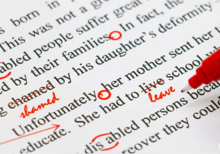 Picture of a person editing a persons book to see if there is any errors. The editor has a red circle on some of the words to make sure the grammar is correct.